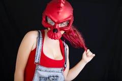 Una mujer joven en guardapolvos del dril de algod?n y casco biking rojo en fondo negro imagenes de archivo