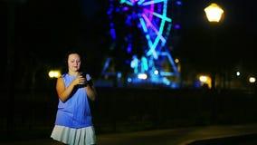 Una mujer joven en la costa escribe un mensaje en el teléfono contra un fondo del cielo nocturno