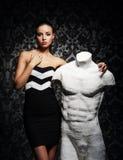 Una mujer joven en la moda viste la presentación con un maniquí Imagen de archivo
