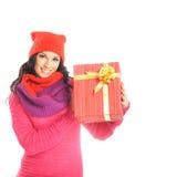Una mujer joven en la ropa roja que lleva a cabo un presente Fotos de archivo