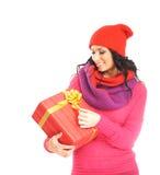 Una mujer joven en la ropa roja que lleva a cabo un presente Imagen de archivo libre de regalías