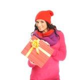 Una mujer joven en la ropa roja que lleva a cabo un presente Fotografía de archivo libre de regalías