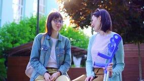 Una mujer joven en las muletas que se sientan en un banco con un amigo en el parque, un día soleado metrajes