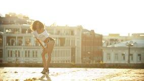 Una mujer joven en los pequeños pantalones cortos que realizan el baile atractivo atractivo en el tejado - jugando sus caderas -  almacen de metraje de vídeo
