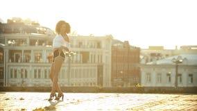 Una mujer joven en los pequeños pantalones cortos que realizan el baile atractivo atractivo en el tejado - puesta del sol brillan almacen de video