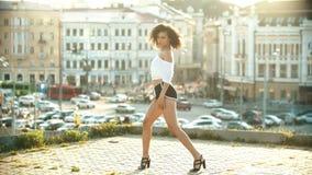 Una mujer joven en los pequeños pantalones cortos que realizan el baile atractivo en el tejado - puesta del sol almacen de metraje de vídeo