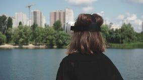 Una mujer joven en los vidrios de la realidad virtual que miran la construcción de la ciudad metrajes