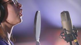 Una mujer joven en los vidrios que registran una canción en el estudio
