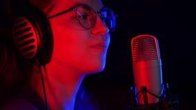 Una mujer joven en los vidrios y los auriculares que registran una canción en el estudio