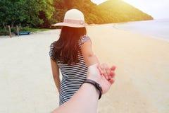 Una mujer joven en una playa lleva a cabo una mano del ` s del hombre Foto de archivo libre de regalías