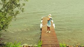 Una mujer joven en ropa brillante se coloca en el embarcadero en la tormenta y mira el relámpago que brilla almacen de metraje de vídeo