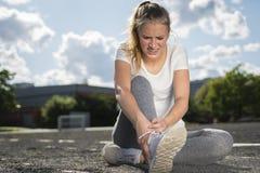 Una mujer joven en ropa de deportes hirió su tobillo mientras que el hacer se divierte foto de archivo