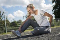 Una mujer joven en ropa de deportes se está sentando en el campo de deportes y parece dolorosa Imágenes de archivo libres de regalías