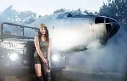 Una mujer joven en ropa militar acerca a un aeroplano fotografía de archivo