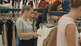 Una mujer joven en una tienda grande elige la nueva ropa para sí misma metrajes