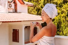 Una mujer joven en una toalla blanca se coloca en el balcón imagenes de archivo