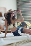 Una mujer joven en un bañador amarillo y un sombrero de paja se está sentando en una cama en una habitación imagen de archivo