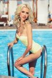 Una mujer joven en un bikini que presenta por la piscina imagen de archivo