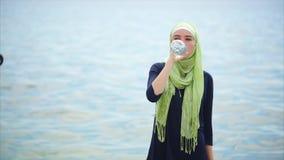Una mujer joven en un hijab bebe el agua mineral de la botella en un día caliente al aire libre almacen de metraje de vídeo