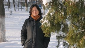 Una mujer joven en un parque con el abeto en la calle, manos toca las ramas de árboles, examinándolos Invierno de la estación metrajes