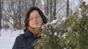 Una mujer joven en un parque con el abeto en la calle, manos toca las ramas de árboles, examinándolos Invierno de la estación almacen de video