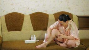 Una mujer joven en un sofá quita la cera de la piel de sus piernas con una servilleta almacen de metraje de vídeo
