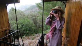 Una mujer joven en un sombrero de paja que disfruta de viajar en un tren viejo almacen de video