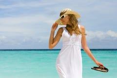Una mujer joven en un sombrero en una playa Imagenes de archivo