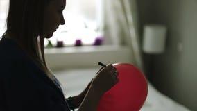 Una mujer joven en un sombrero festivo escribe enhorabuena en un globo rojo metrajes