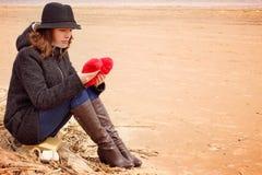 Una mujer joven en un sombrero y una capa se sienta en la orilla de la bahía en una red de pesca con un corazón de la felpa en su Imagen de archivo