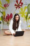 Una mujer joven en un traje blanco con la computadora portátil Fotos de archivo