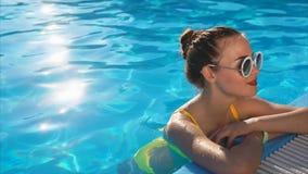 Una mujer joven en un traje de baño está en la piscina con agua fresca, un día de verano caliente metrajes