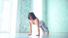 Una mujer joven en un traje del deporte, realiza los ejercicios para la flexibilidad, señora contratada a yoga en la estera Mucha almacen de metraje de vídeo