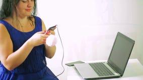 Una mujer joven en un vestido azul está escuchando la música en los auriculares de su teléfono almacen de video