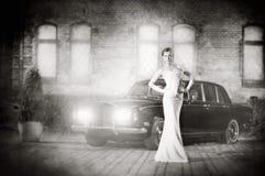 Una mujer joven en un vestido blanco en un fondo luxorious Foto de archivo libre de regalías