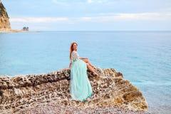 Una mujer joven en un vestido de la menta se sienta en una piedra grande en la orilla del mar adriático Fotos de archivo libres de regalías