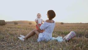 Una mujer joven en un vestido ligero se está sentando en la hierba en el campo y los juegos con un bebé precioso Madre feliz con  almacen de metraje de vídeo