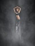 Una mujer joven en un vestido negro en un fondo de niebla Foto de archivo libre de regalías