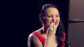 Una mujer joven en un vestido rojo con la barra de labios roja quita exceso de maquillaje con un cojín de algodón almacen de metraje de vídeo