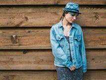 Una mujer joven en vaqueros cerca de la pared de madera Fotos de archivo libres de regalías