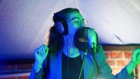 Una mujer joven en vidrios y auriculares que canta en el estudio Iluminación de neón metrajes