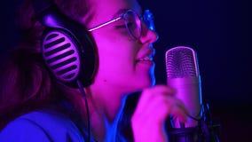 Una mujer joven en vidrios y auriculares viene al soporte del micrófono y comienza a cantar Iluminación de neón púrpura almacen de metraje de vídeo