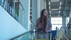 Una mujer joven en vidrios y una capa sostiene un teléfono metrajes