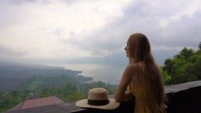 Una mujer joven en una visita amarilla del vestido y del sombrero un punto de vista con una opinión sobre una montaña Batur y él  metrajes