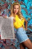 Una mujer joven encantadora en una blusa amarilla con un periódico Imagenes de archivo
