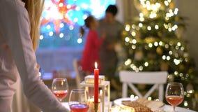 Una mujer joven enciende las velas en la tabla de la Navidad almacen de metraje de vídeo