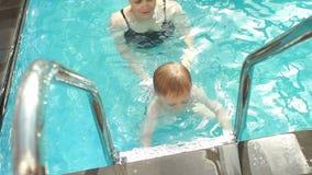 Una mujer joven enseña a un niño joven a zambullirse en el agua C?mara lenta metrajes