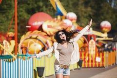 Una mujer joven es feliz y salta Imagen de archivo libre de regalías