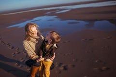 Una mujer joven es que sienta y de abarcamiento de su pequeño hijo Foto de archivo