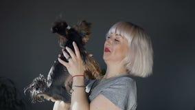 Una mujer joven es sonrisas y juego con su perro Yorkshire Terrier a manos de una muchacha feliz en la sala de estar almacen de metraje de vídeo
